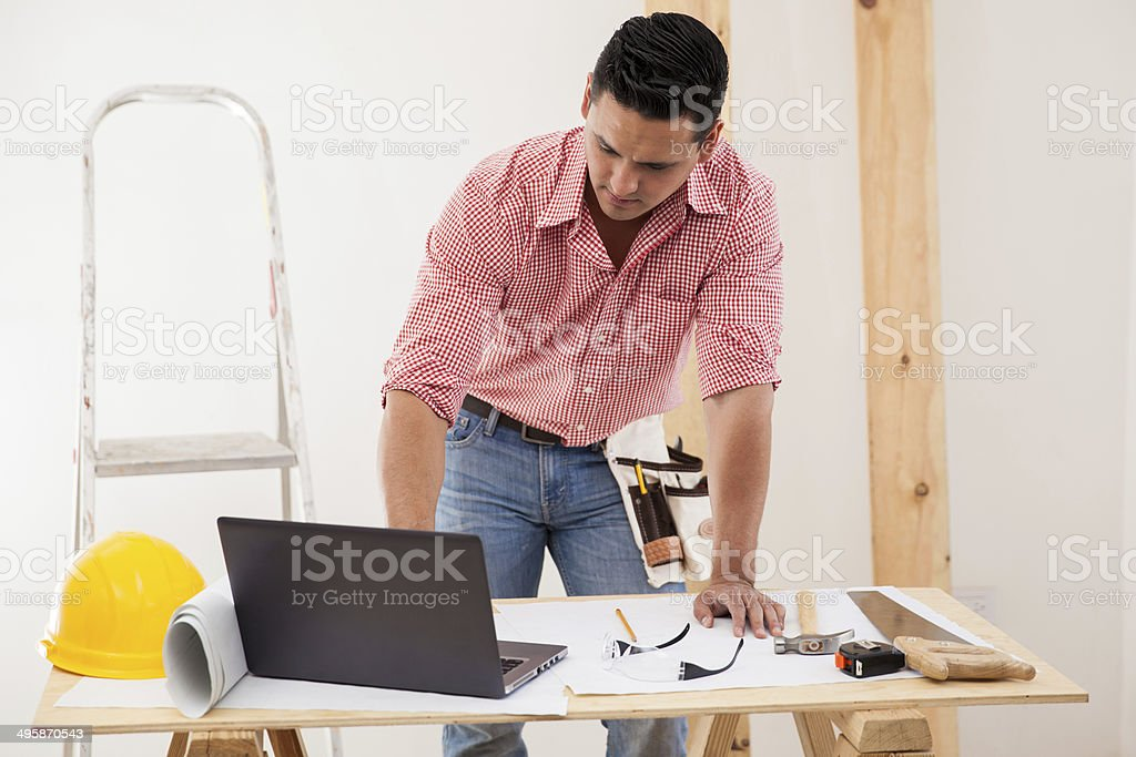 Contractor using a laptop at work Young Latin contractor reviewing the floor plan on a laptop at work Laptop Stock Photo