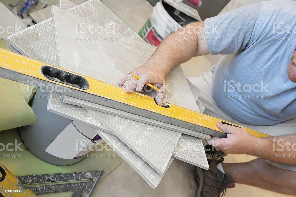 Instalador utilizando un nivel para azulejos de medida foto de stock libre de derechos