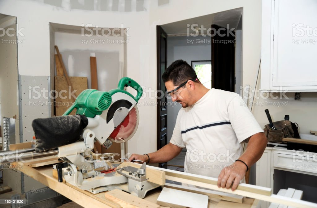 A contractor using a saw in a kitchen being remodeled royalty-free stock photo