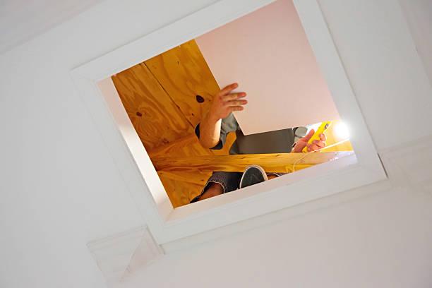 contractor working in attic - kruipruimte stockfoto's en -beelden