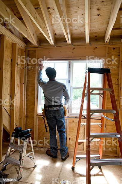 Contractor Working On Window In New Home Stock Photo - Download Image Now