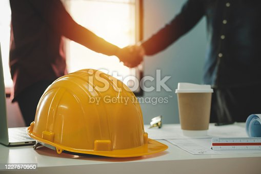 1055059750 istock photo Contractor. yellow safety helmet on workplace desk with construction worker team hands shaking greeting start up plan new project contract in office center at construction site, partnership concept 1227570950
