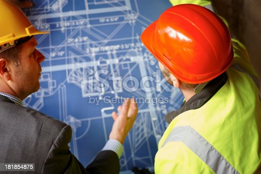 istock Contractors discussing over a blueprints on construction site 181854875