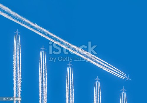 istock Contrails and airplanes forming financial graph 1071072396