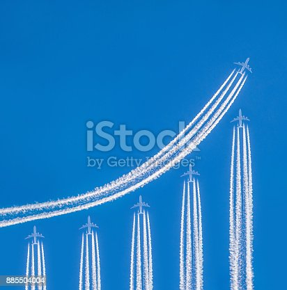 istock Contrails and airplanes forming financial graph 885504004