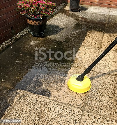 istock Contrast between clean and dirty patio slabs being pressure washed 1285633555