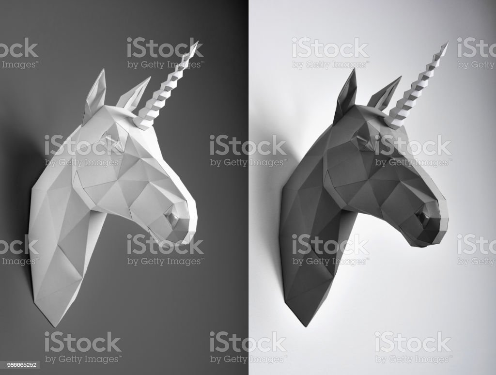 Contrast collage of black and white paper unicorn heads. stock photo