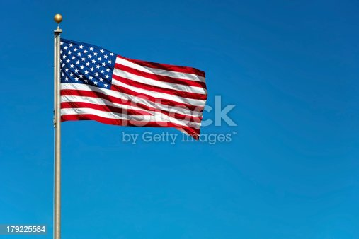 579407234istockphoto Contrast photo American flag waving against solid blue sky 179225584
