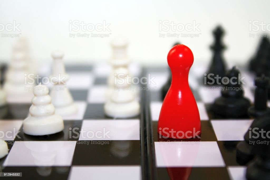 Contrast red black white colored chess concept, bright red ludo figure on the chessboard, metaphor policy politics or business themes. stock photo