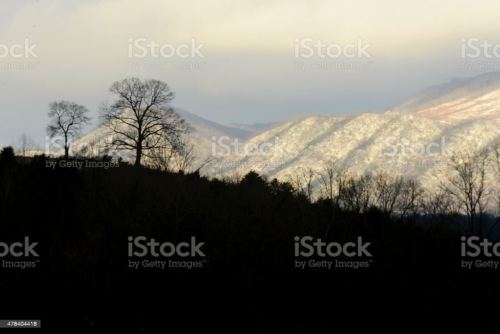 Contrast snow covered mountains and dark silhouettes. stock photo
