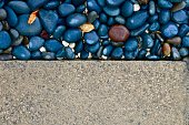 Contrast textures of a paved driveway and pebbled sidewalk. Background image.