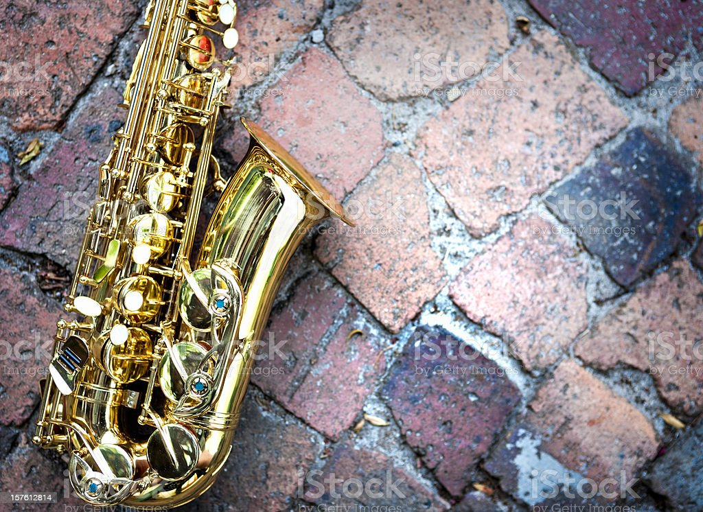 Contrasting textures: gleaming golden sax on rough raw bricks stock photo