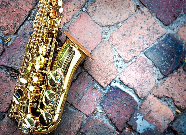 kontrastierende strukturen: glänzend goldenen sax auf unebenem raw-bausteinen spielen - altsaxophon stock-fotos und bilder