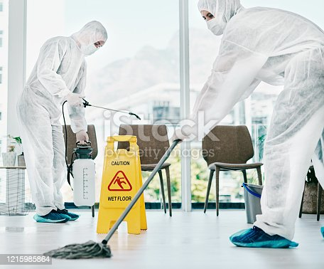 Shot of healthcare workers wearing hazmat suits and sanitising a room during an outbreak