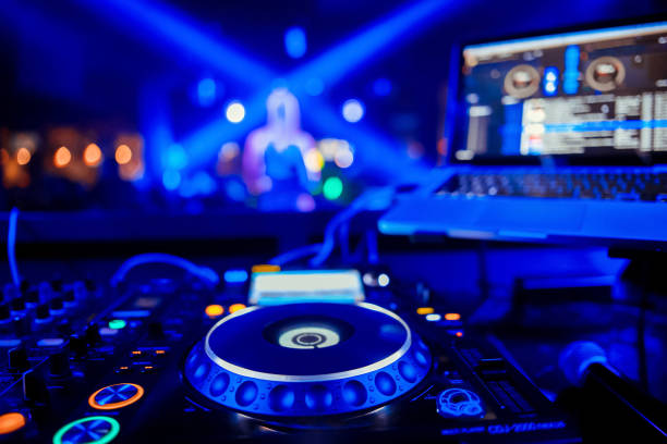 control DJ for mixing music with blurred people dancing at party in nightclub control DJ for mixing music with blurred people dancing at party in nightclub dj stock pictures, royalty-free photos & images