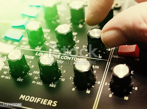A hand turns a knob on the control panel of a retro-style analog synthesizer.
