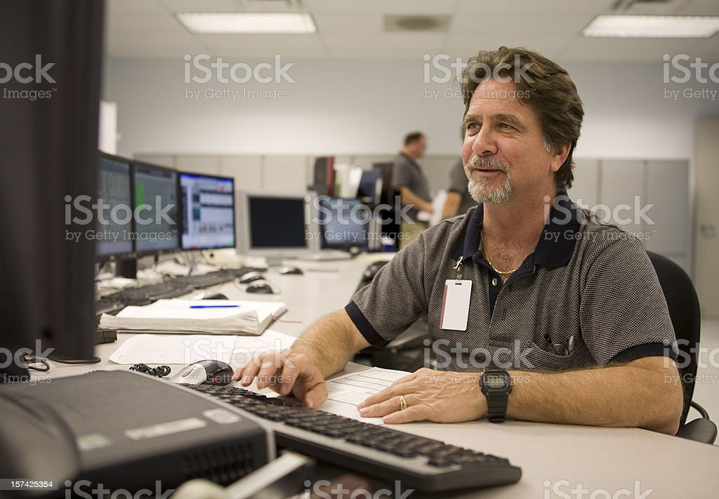 Control Room Operator Working at Computer stock photo