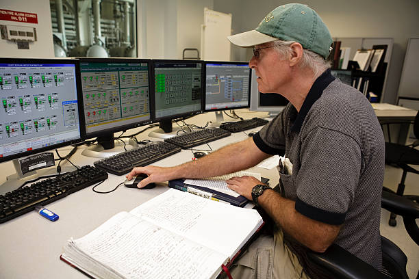 Control Room Technician Intensely Working on Computers stock photo