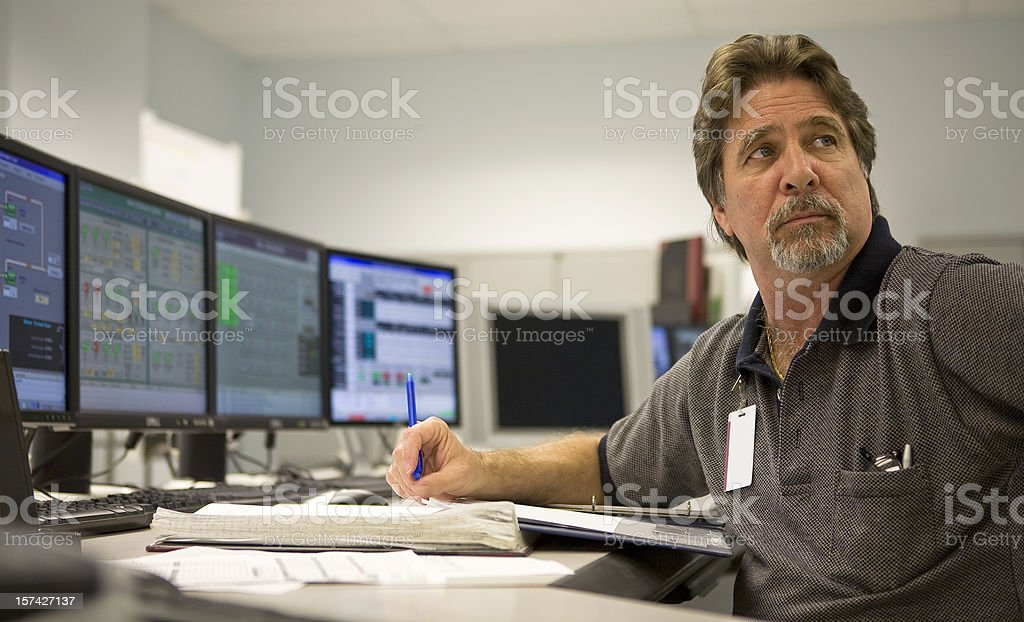Control Room Technician Working at Computer Station stock photo