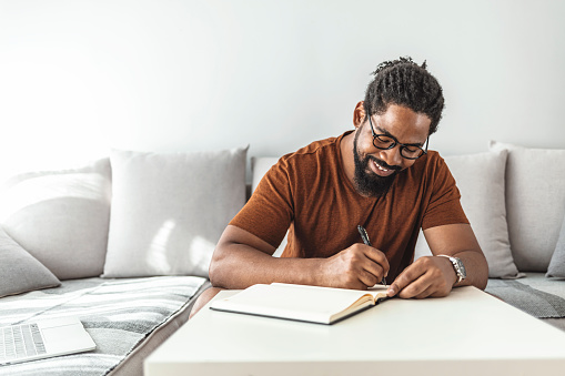 Image of happy African man with notepad and pen sitting on sofa.