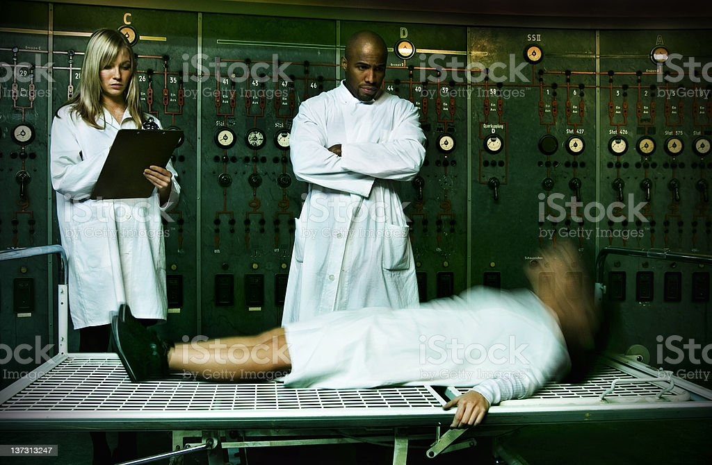 Controlled awakening Young woman rising under control of lab workers. Long exposure. African Ethnicity Stock Photo