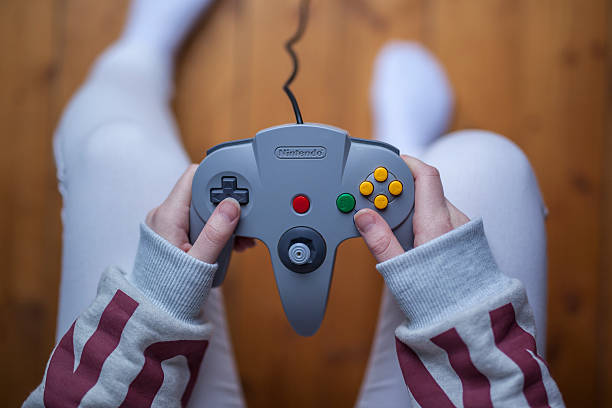 N64 Controller - Nintendo Game Controller Gothenburg, Sweden - January 11, 2015: A shot from above of a young woman's hands holding a game pad controller for the Nintendo 64 video game console developed by Nintendo Co., Ltd. The young woman has tattoos on her arms. Natural lighting. Shot on wooden background. nintendo stock pictures, royalty-free photos & images