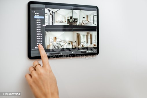 Controlling home with video cameras and digital tablet. Concept of remote video surveillance over the internet with smart touch screen devices