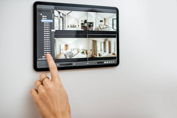 Controlling home with video cameras and digital tablet stock photo