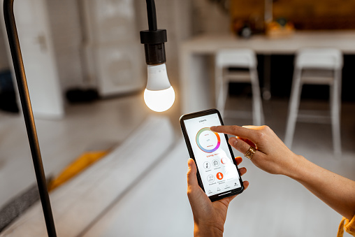 Controlling light bulb temperature and intensity with a smartphone application. Concept of a smart home and managing light with mobile devices