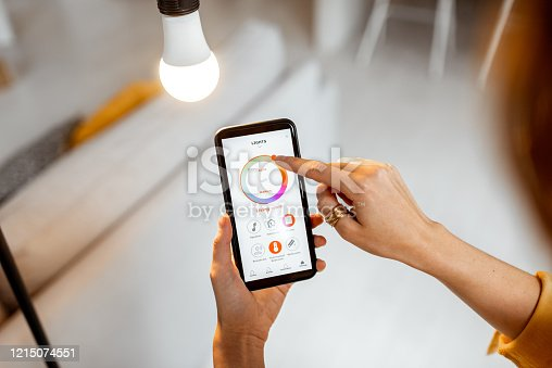 istock Controlling light bulb with mobile device 1215074551