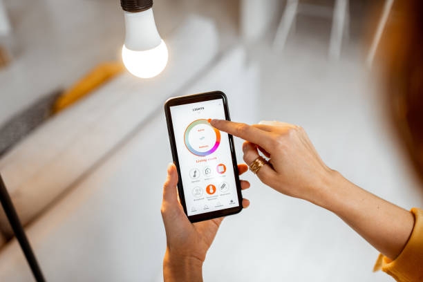 Controlling light bulb with mobile device stock photo