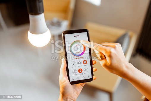 istock Controlling light bulb with mobile device 1215074558