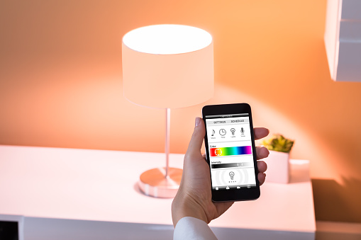 Person Controlling Light With App On Phone