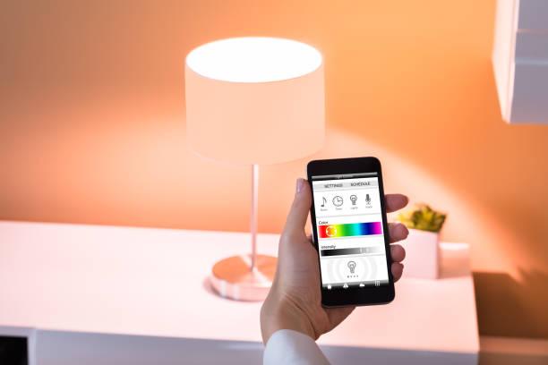 steuerung von licht mit anwendung - nachttischleuchte stock-fotos und bilder