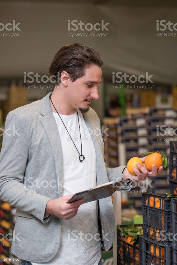 Man qontrolling orange quality in a warehouse.