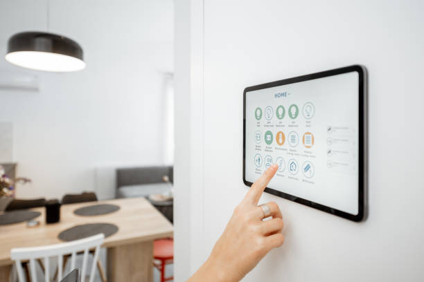 Controlling smart devices with a digital tablet at home stock photo