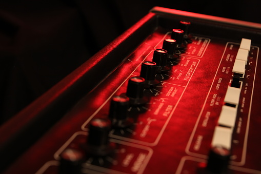 istock Controls of a retro analog music synth in red light 641796588