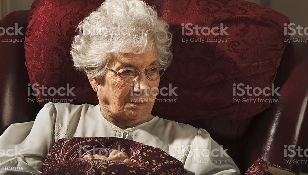 convalescing senior woman sitting in nightie with blanket royalty-free stock photo