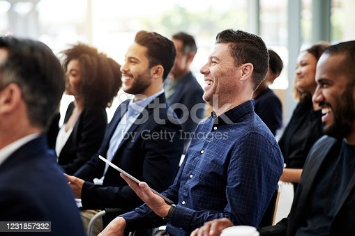 Shot of a businessman using a digital tablet during a conference