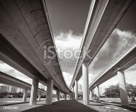 The view from underneath converging concrete transportation structures in Singapore City.