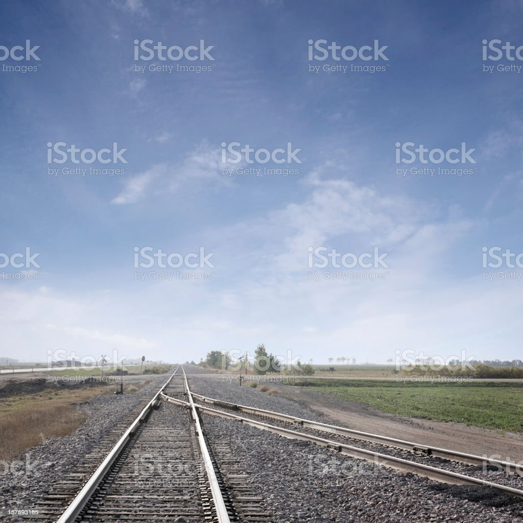 converging train tracks under big sky royalty-free stock photo
