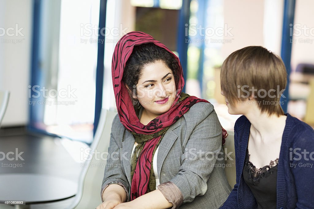 conversation between islam and western style young woman royalty-free stock photo