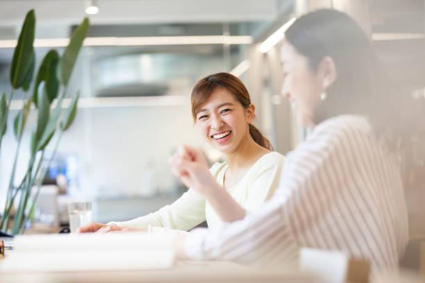 オフィスで会話をする女性たち - 笑顔 女性 ストックフォトと画像