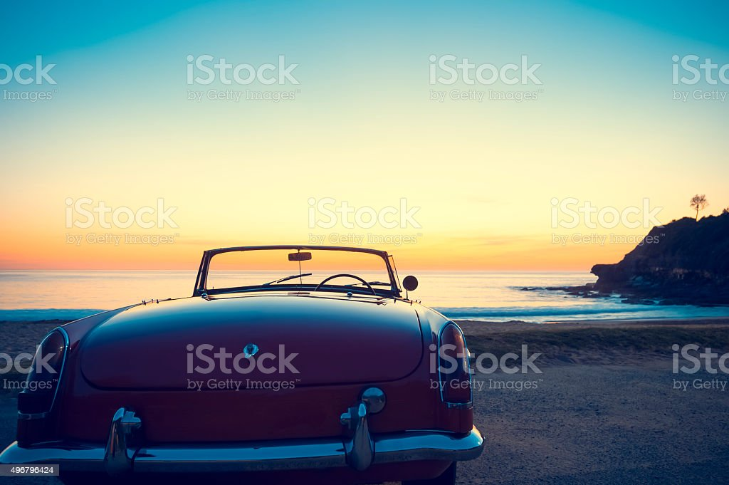 Convertible at the beach at sunset or sunrise. stock photo