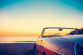 Convertible at the beach at sunset or sunrise.