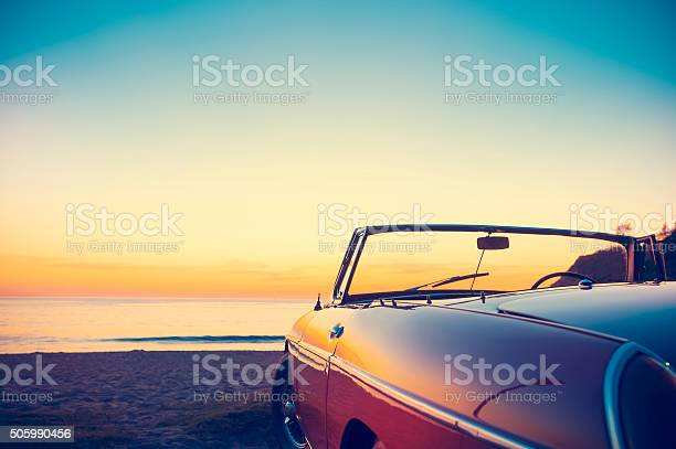 Photo of Convertible at the beach at sunset or sunrise.