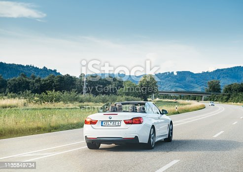 Schiltach, Germany - Jun 10, 2018: German highway with luxury BMW convertible cabriolet car driving fast on the rural highway on a sunny day with Black Forest mountains in background