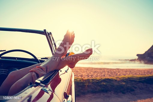 Convertible Car with womans feet hanging out of the window. The car is parked at the beach at sunrise. Very relaxing vacation or road trip image. Car is a convertible. copy space