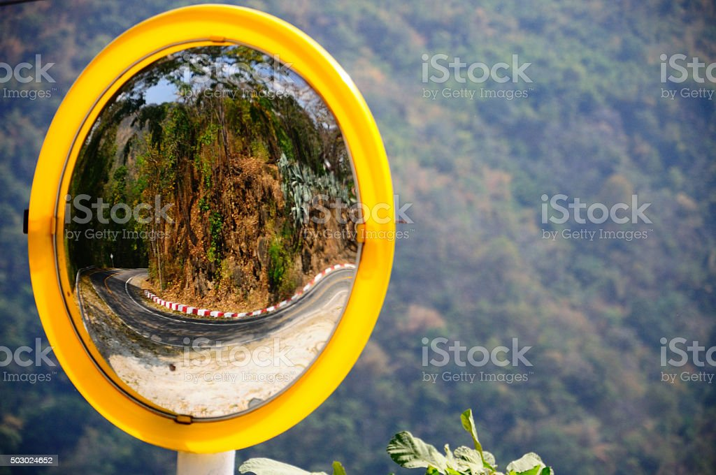 Convex mirror reflecting road curve on mountain stock photo