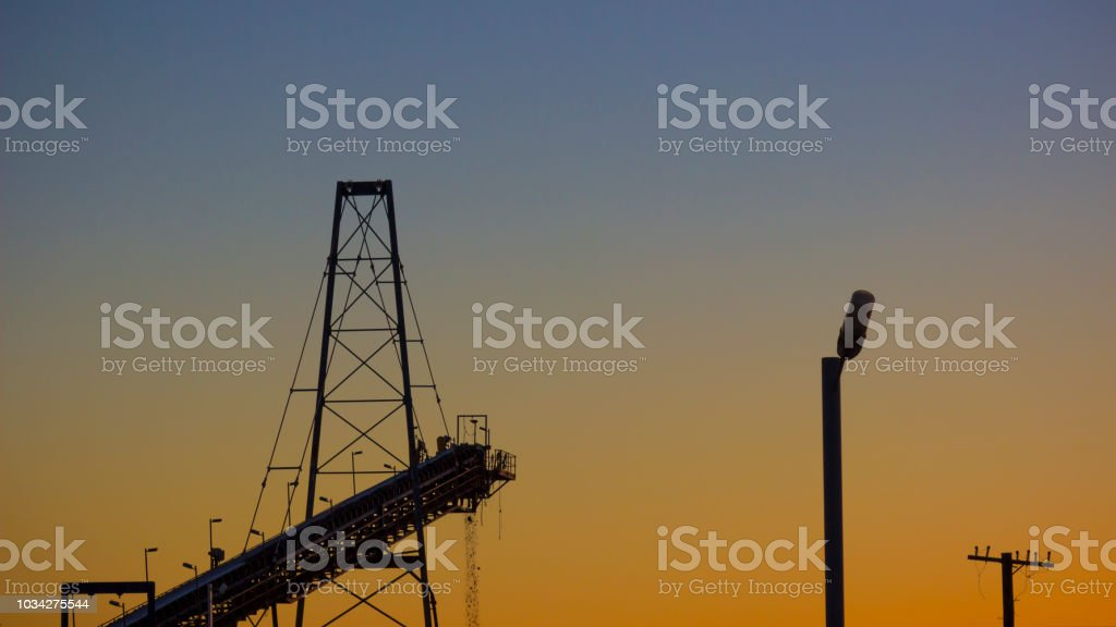 Conveyor belt carrying ore at a mine site processing plant. stock photo
